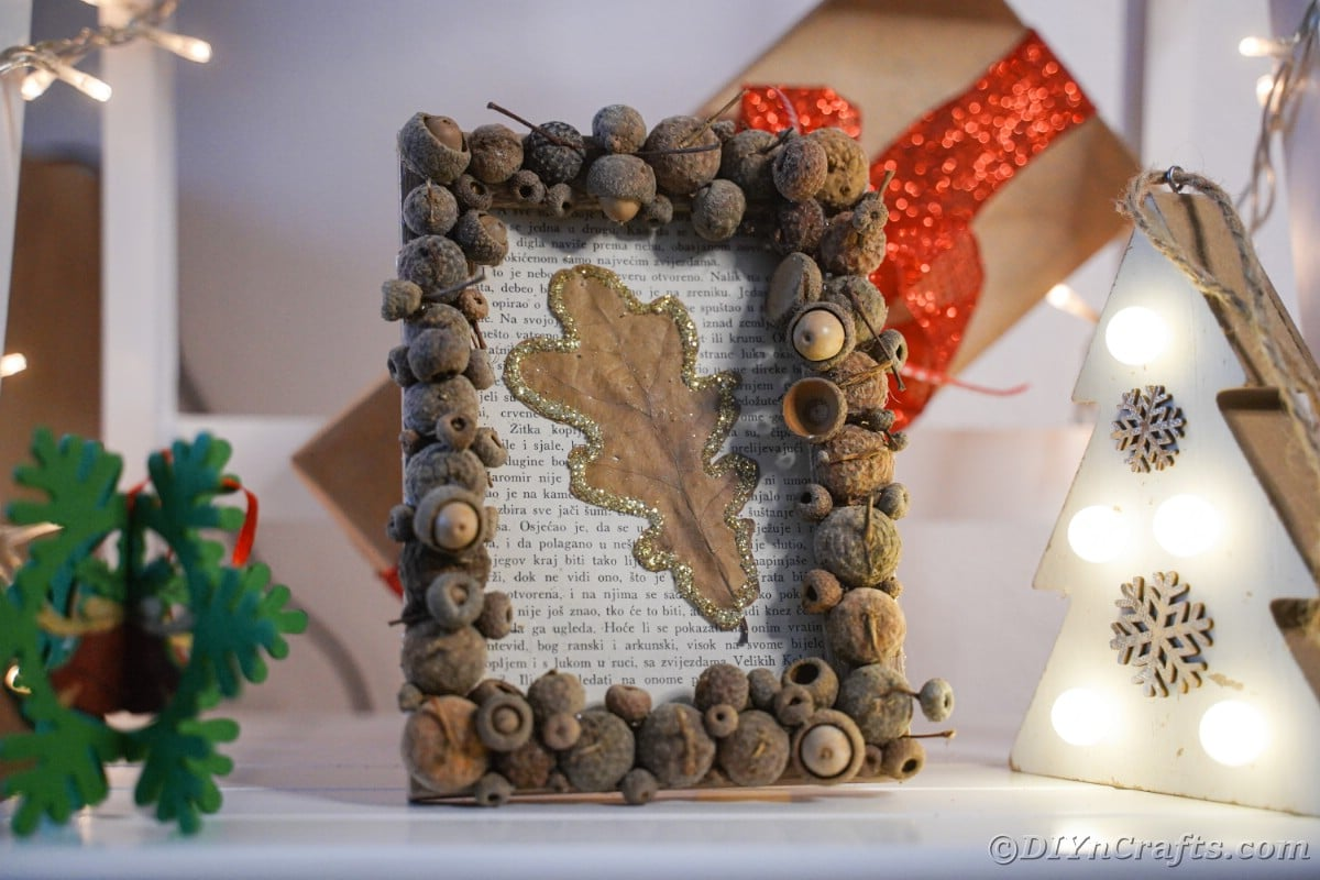 Rustic frame with old book page and leaf on table with gift in background