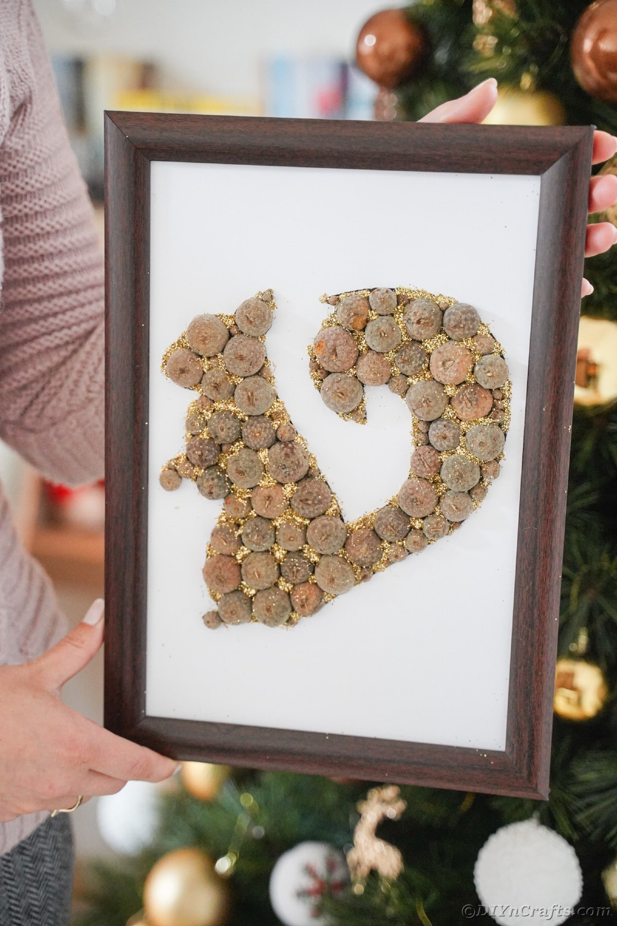 Rustic squirrel picture held by woman in front of Christmas tree
