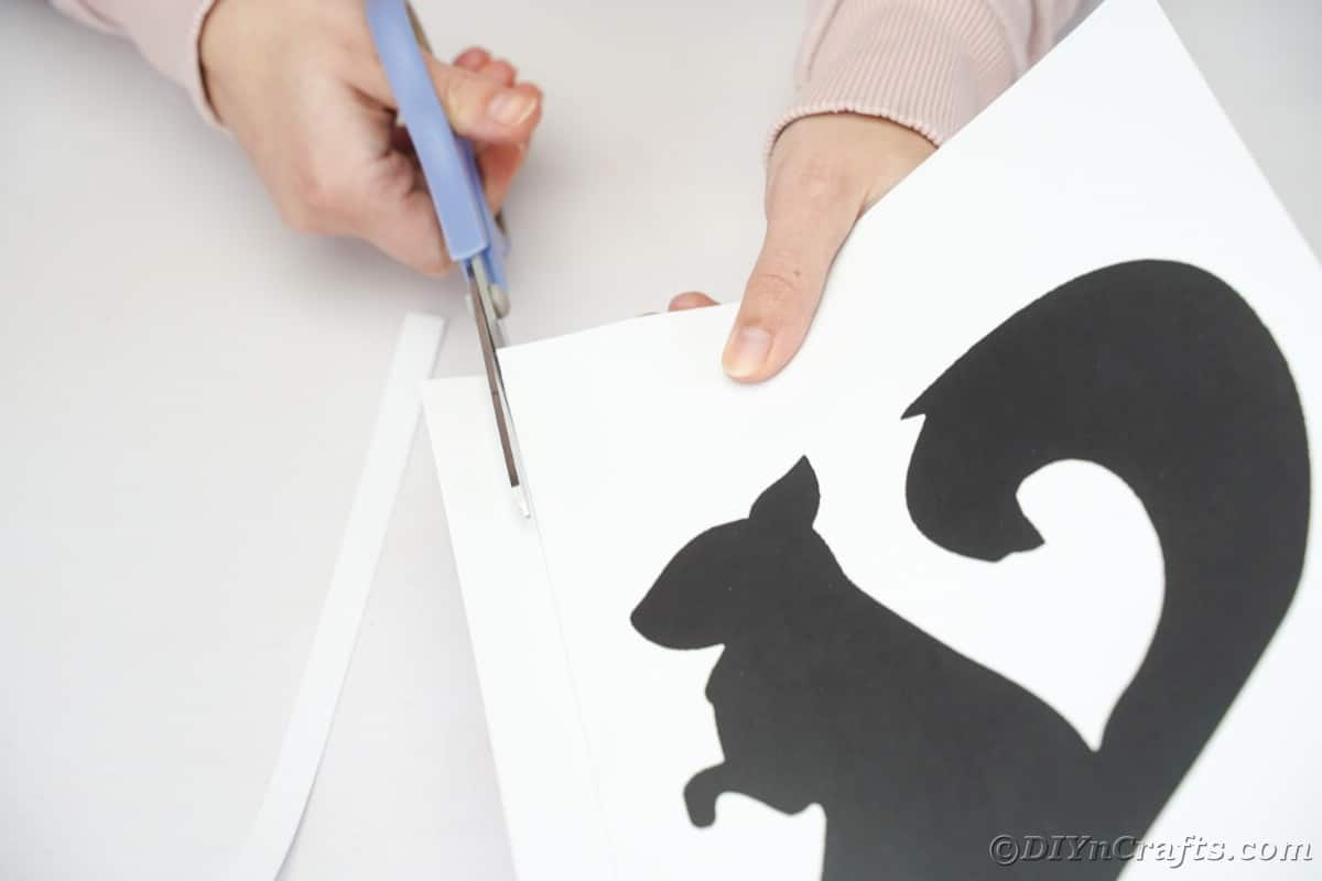 Hand using blue scissor to cut paper with black squirrel printed on it