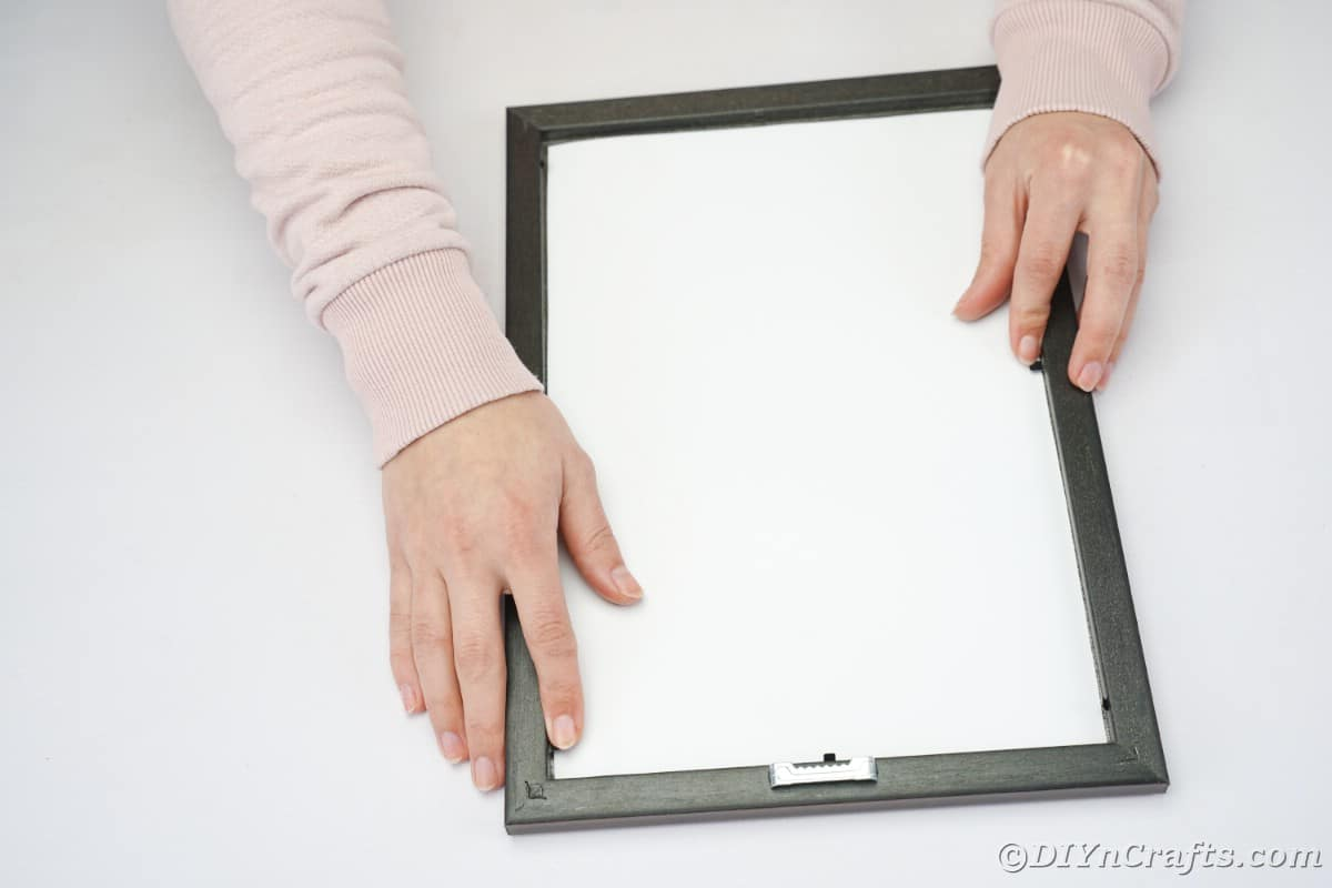 Hands placing paper into picture frame