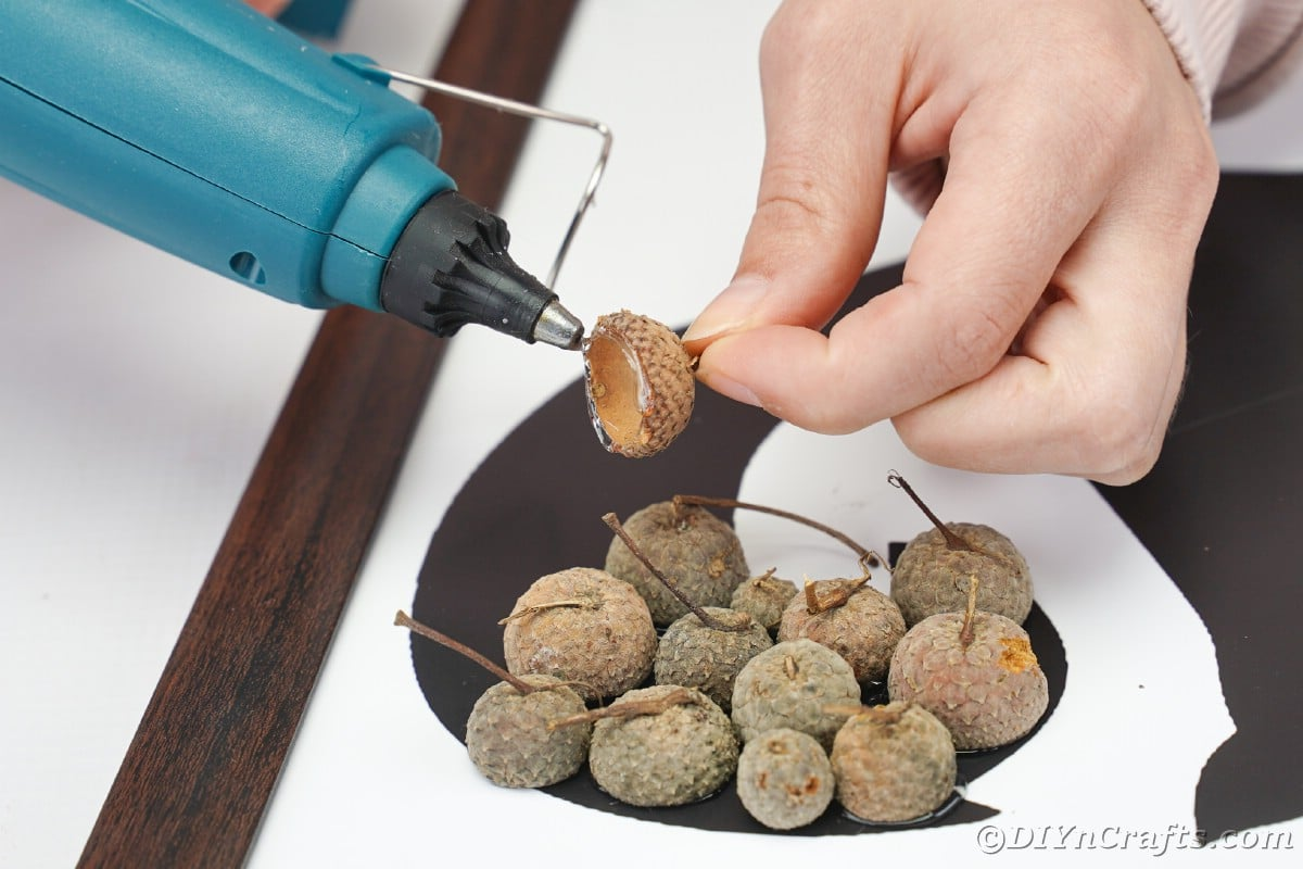 Hand holding acorn cap while hot glue gun applies glue