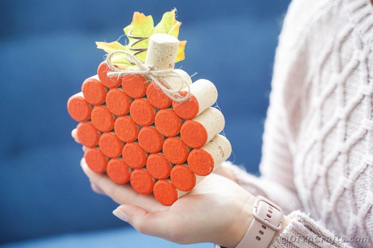 orange pumpkin made of cork in hands