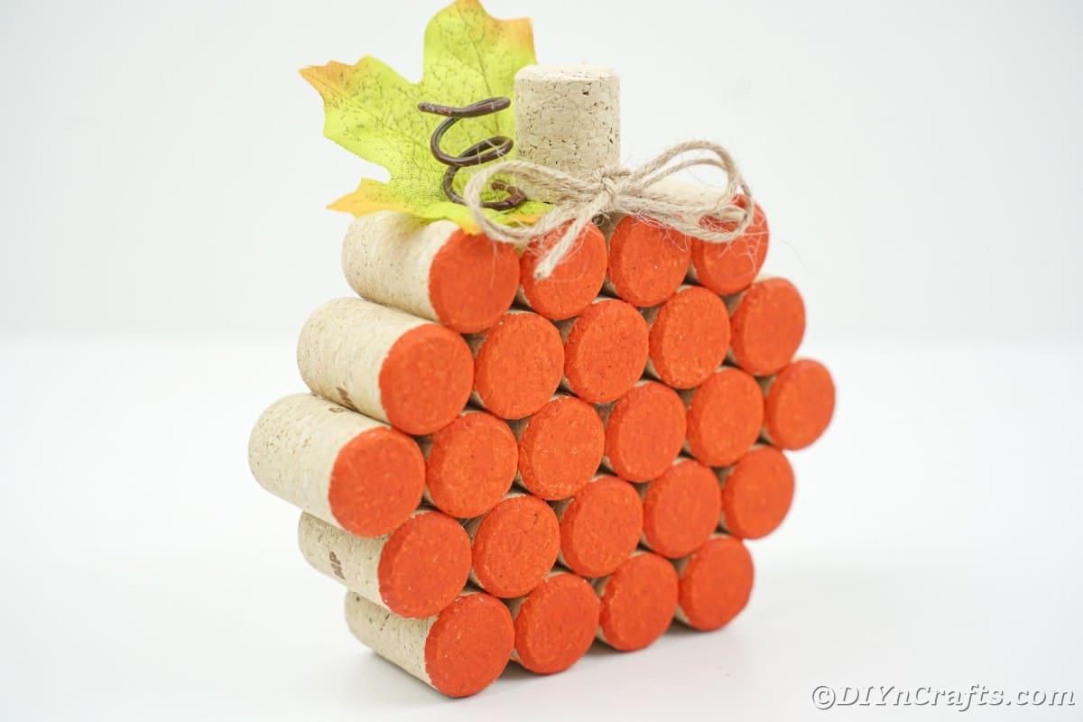side of cork pumpkin painted orange on white table