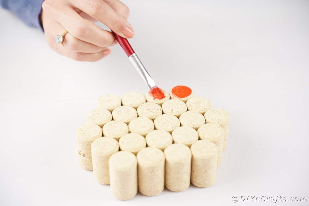 hand painting orange paint onto cork