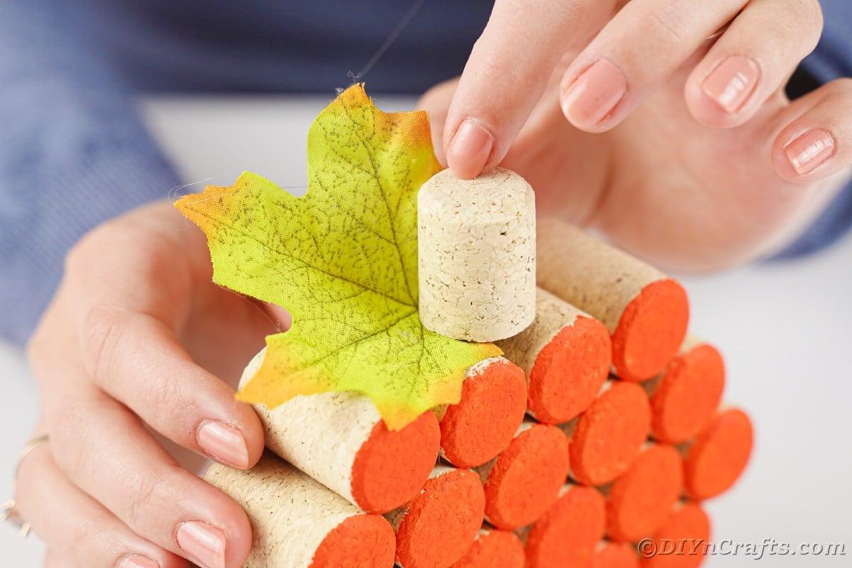hand holding cork on top of pumpkin