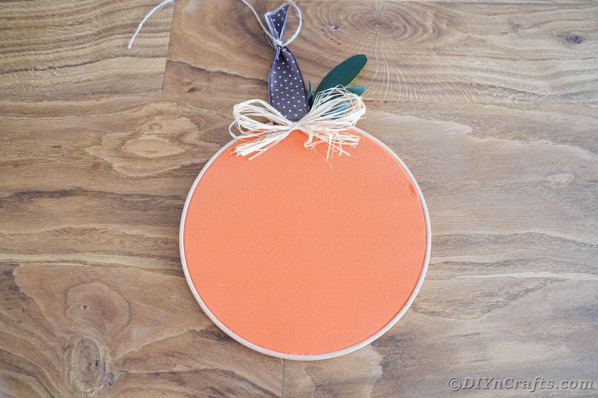 orange cloth pumpkin with raffia bow on the table