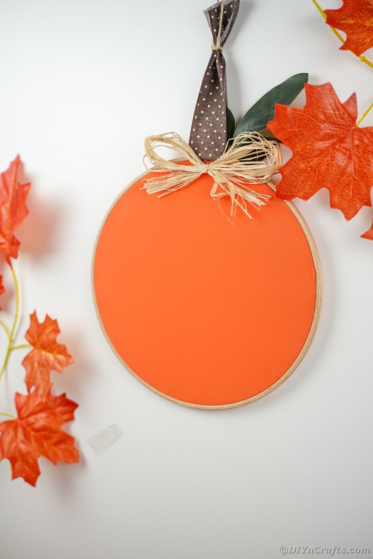 cloth pumpkin on white table with faux leaves