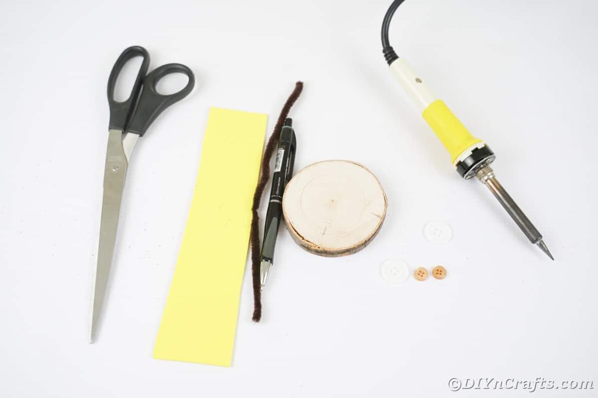 Tesoura, papel amarelo, limpador de cachimbo, fatia de madeira e ferramenta para queima de madeira na mesa branca