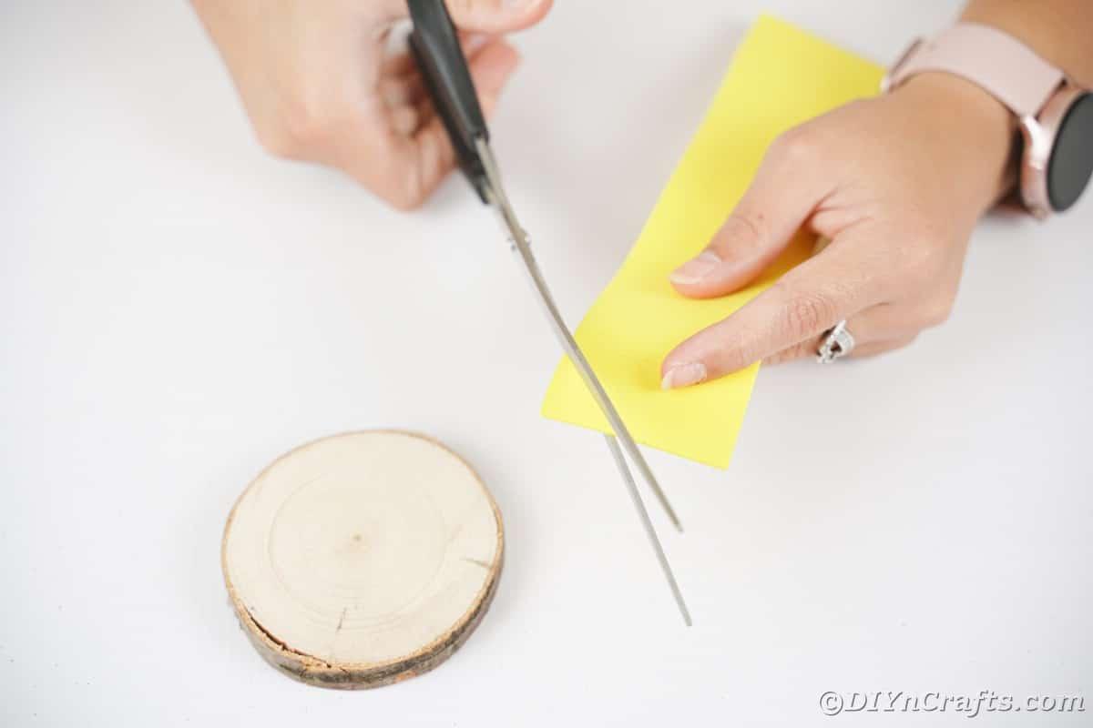 Tesoura azul cortando papel amarelo