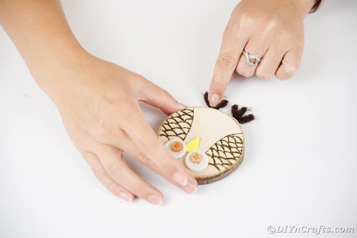 Mão segurando os pés do limpador de cachimbo abaixo da coruja de madeira