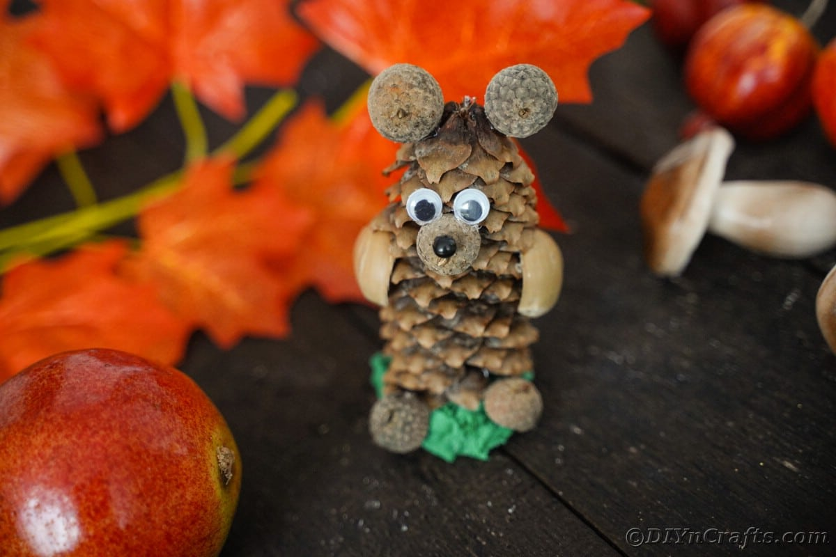 pinecone animal on wood table by fake leaves