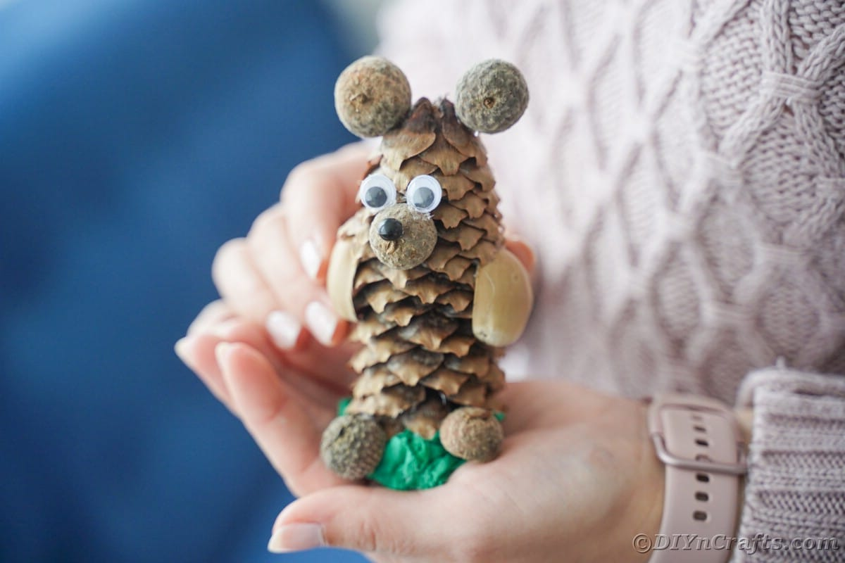 woman holding animal made from pine cone