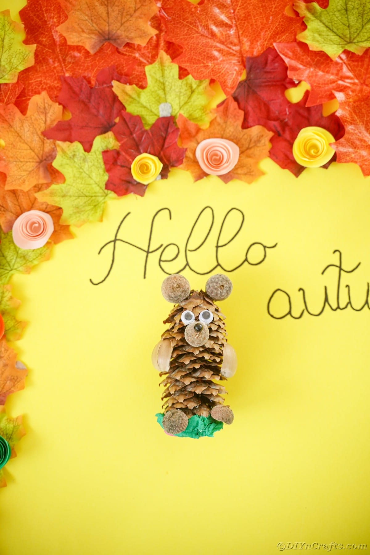 Yellow table with fake leaves and a pinecone bear