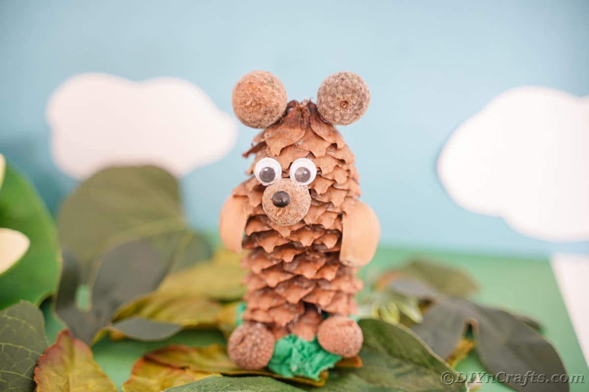 bear made of pine cone and nuts on top of fake leaves