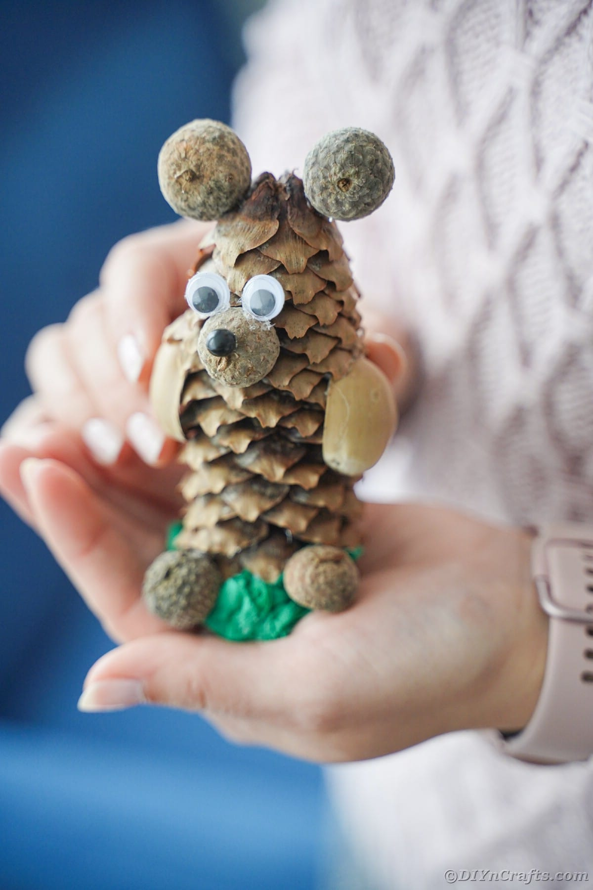 woman in sweater holding pinecone bear