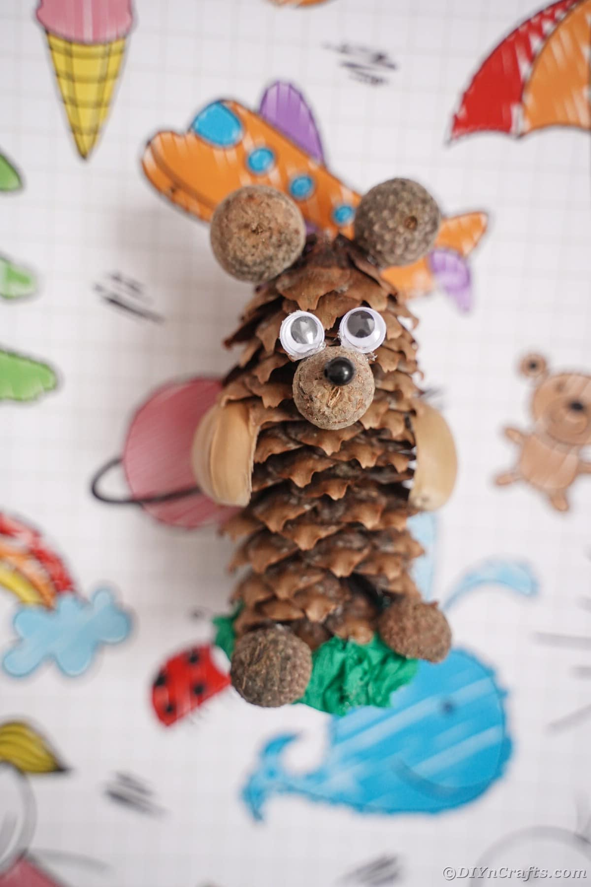 pinecone bear laying on colorful paper