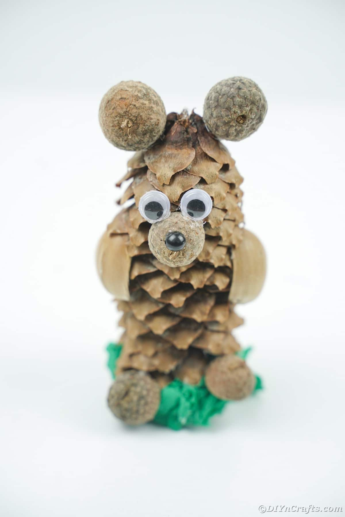 pinecone bear on green base sitting on white table