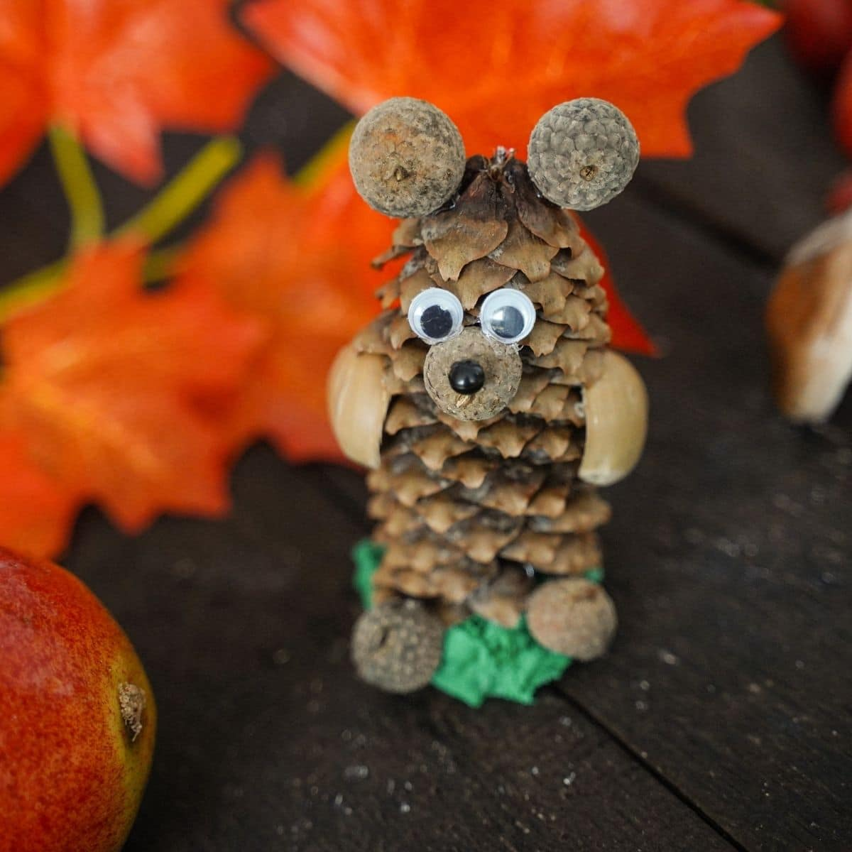 pinecone bear on wood table by fake leaves