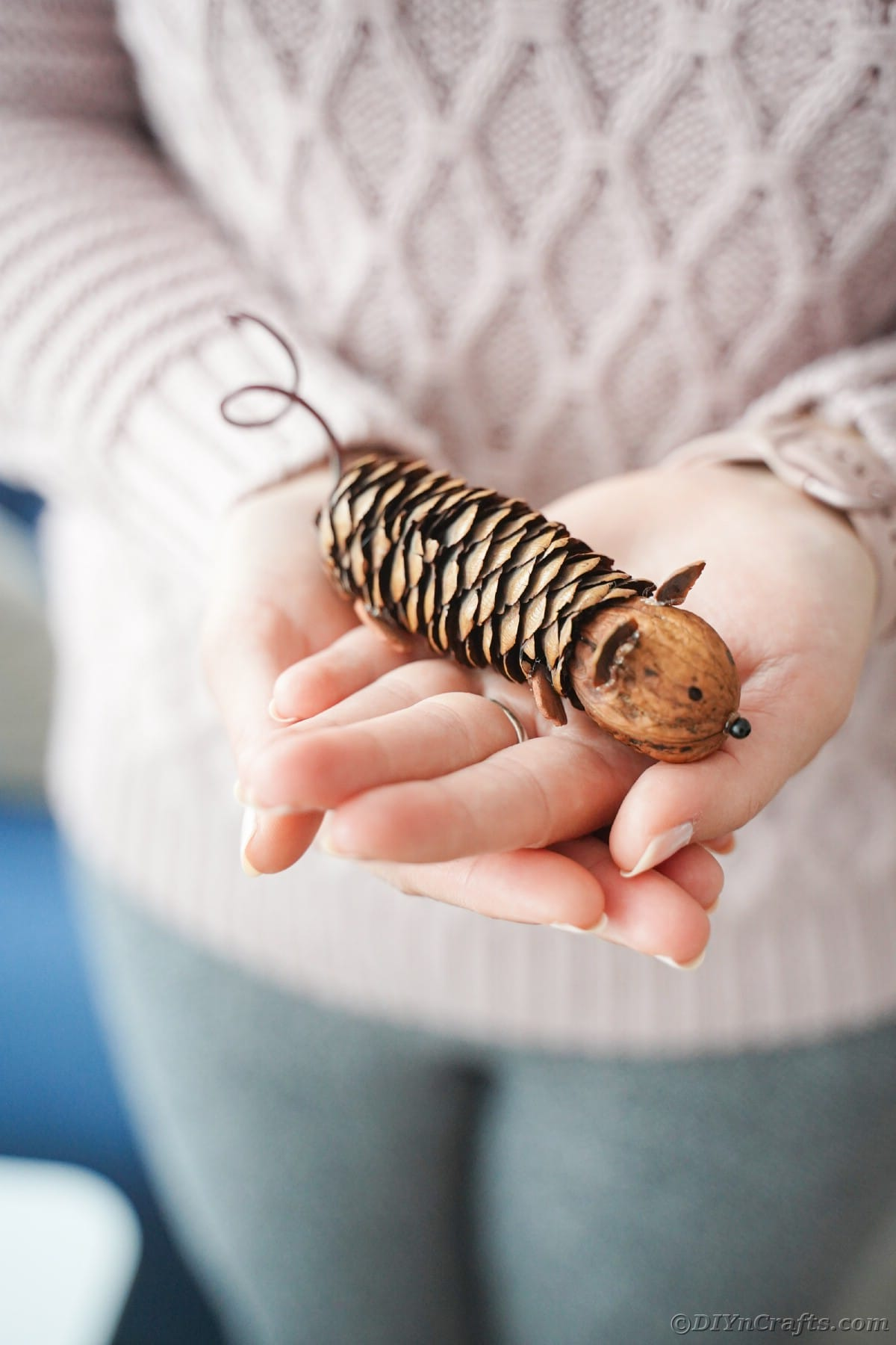 lady in pink sweater holding pinecone mouse in hands