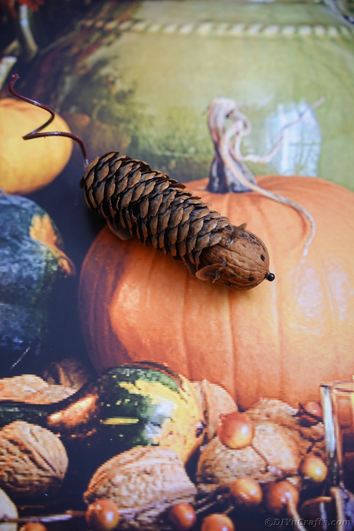 pinecone mouse laying on top of pumpkin paper