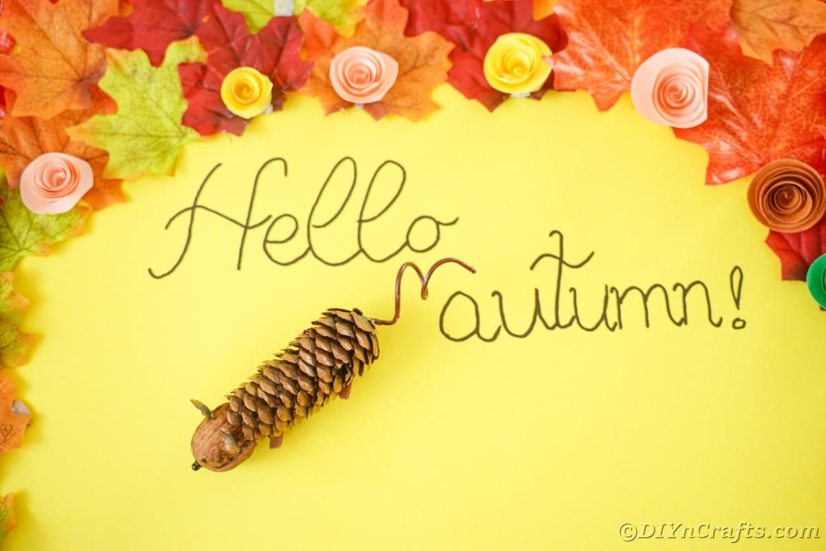 yellow paper with fake leaves saying hello autumn by fake pinecone mouse