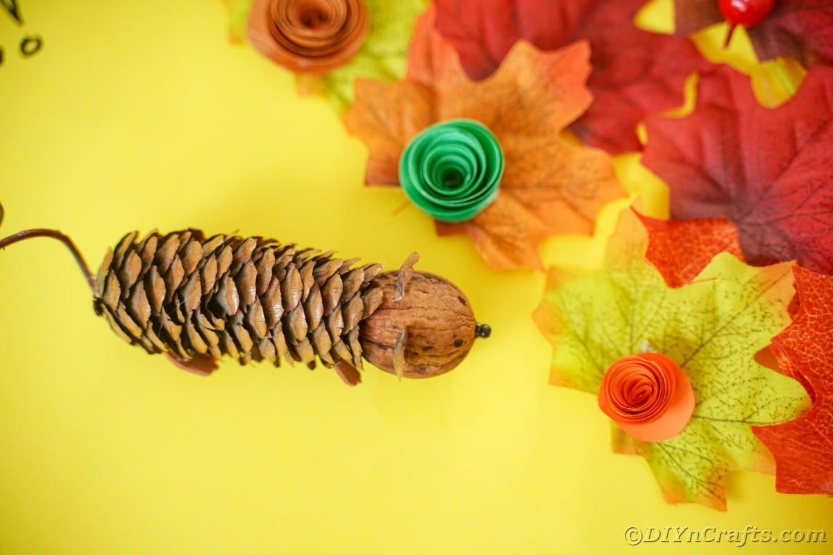 pinecone mouse on yellow paper with fake leaves