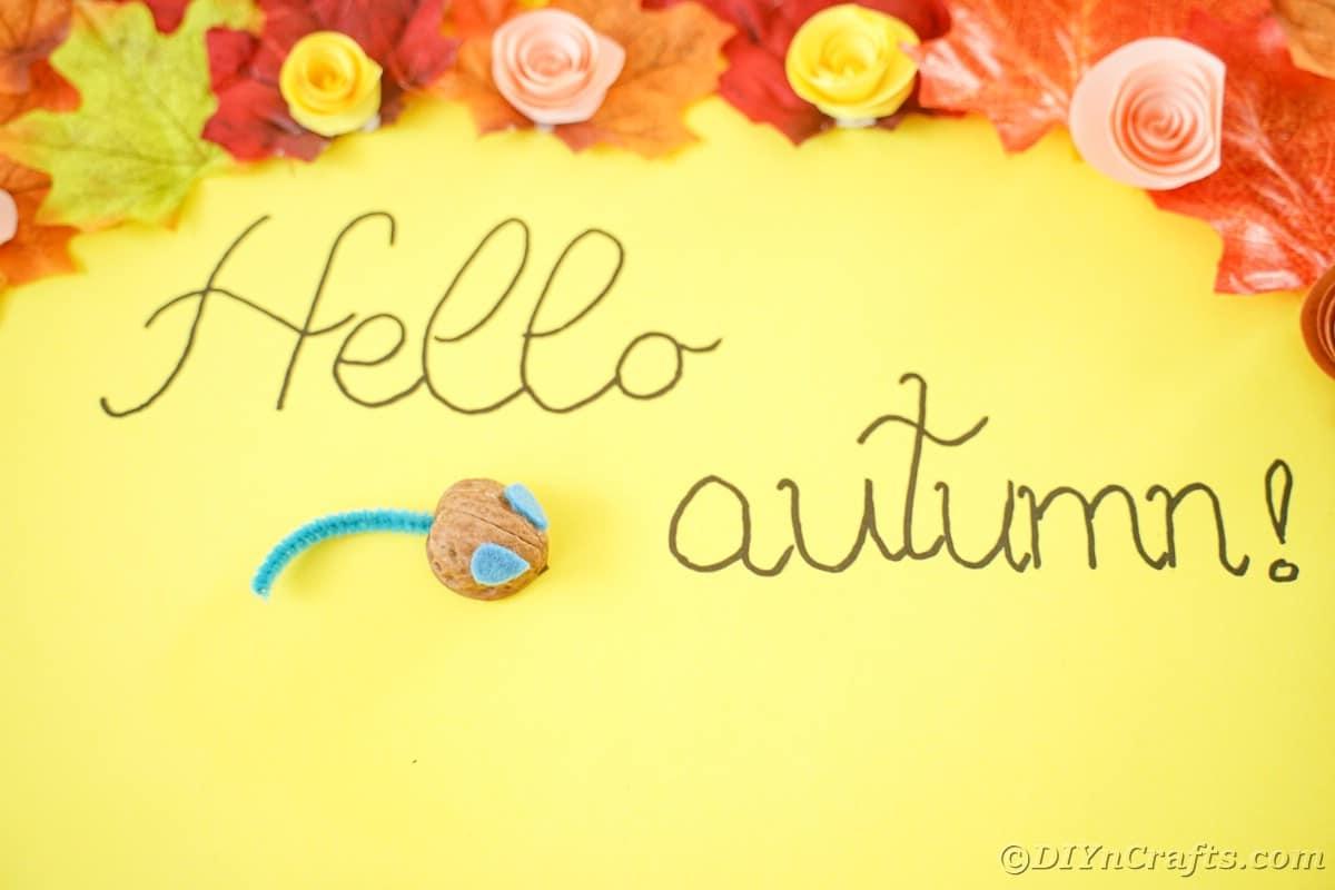 Hellow autumn written on yellow paper next to walnut mouse