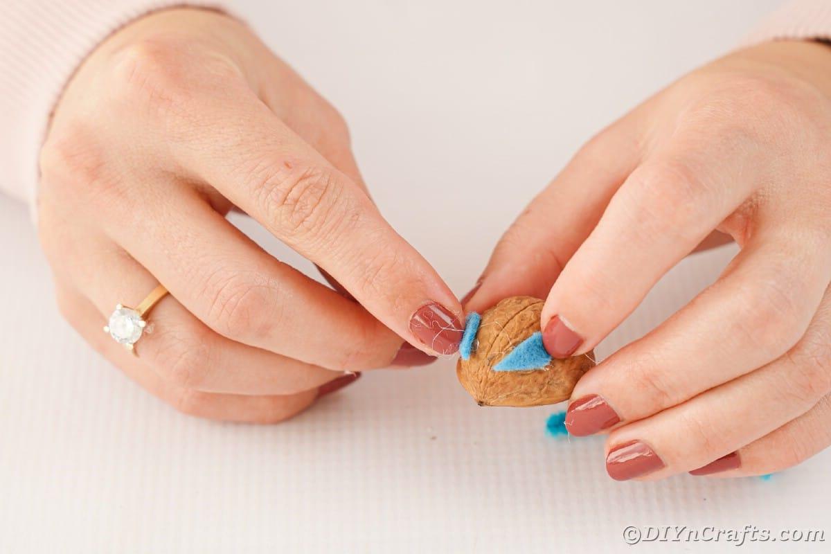 Hands gluing blue ears onto walnut shell