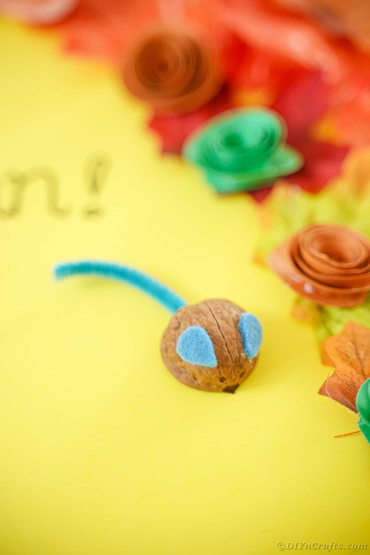 Walnut mouse on yellow paper next to paper flowers