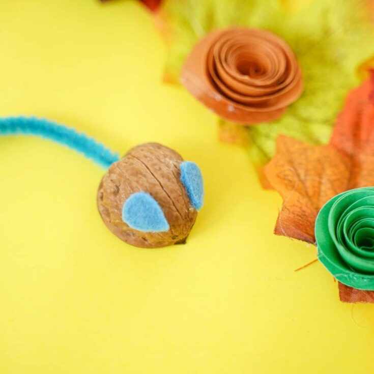 Walnut shell mouse on yellow paper with fake leaves and fake flower