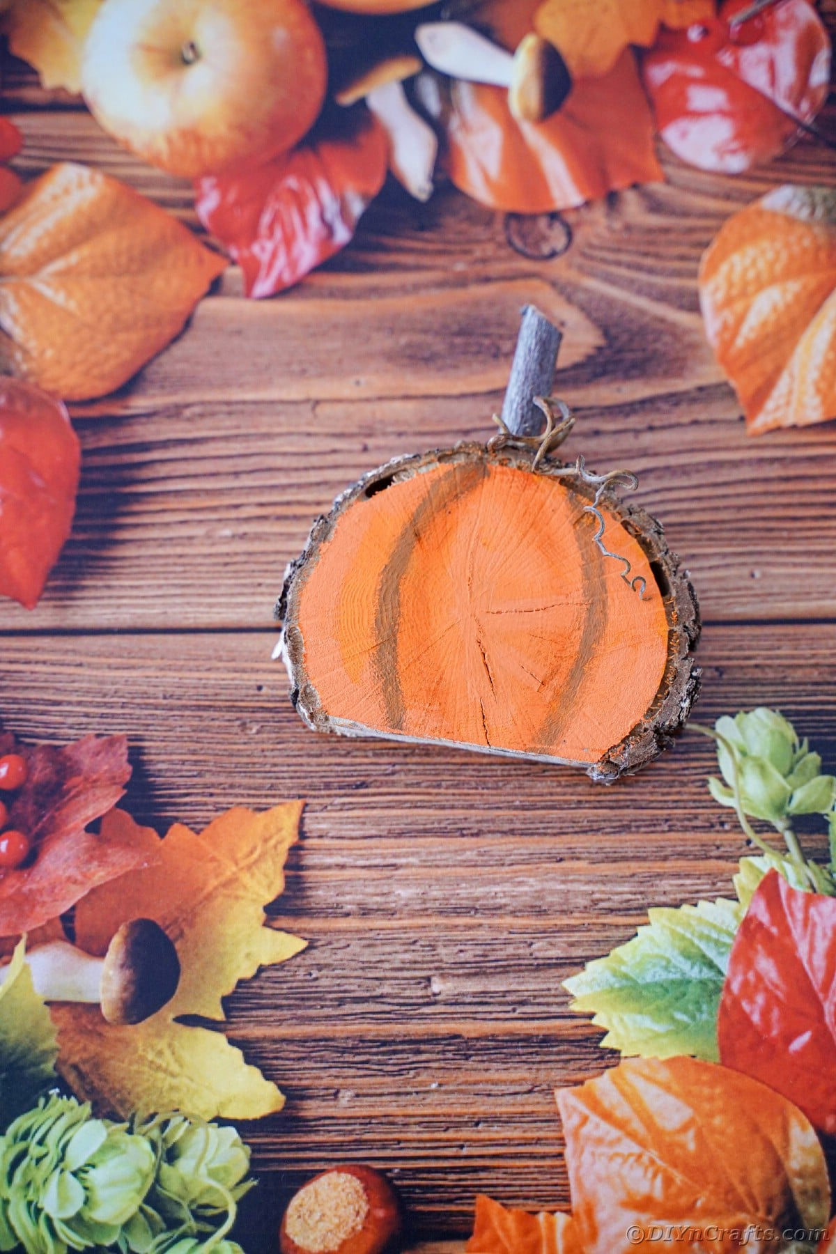 Wood slice pumpkin on wood table with fake fall decor surrounding it