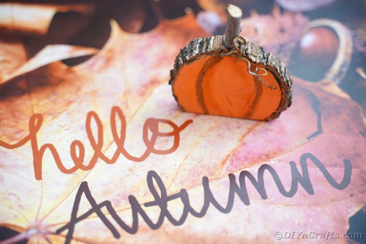 Fake wood pumpkin on paper that says hello autumn