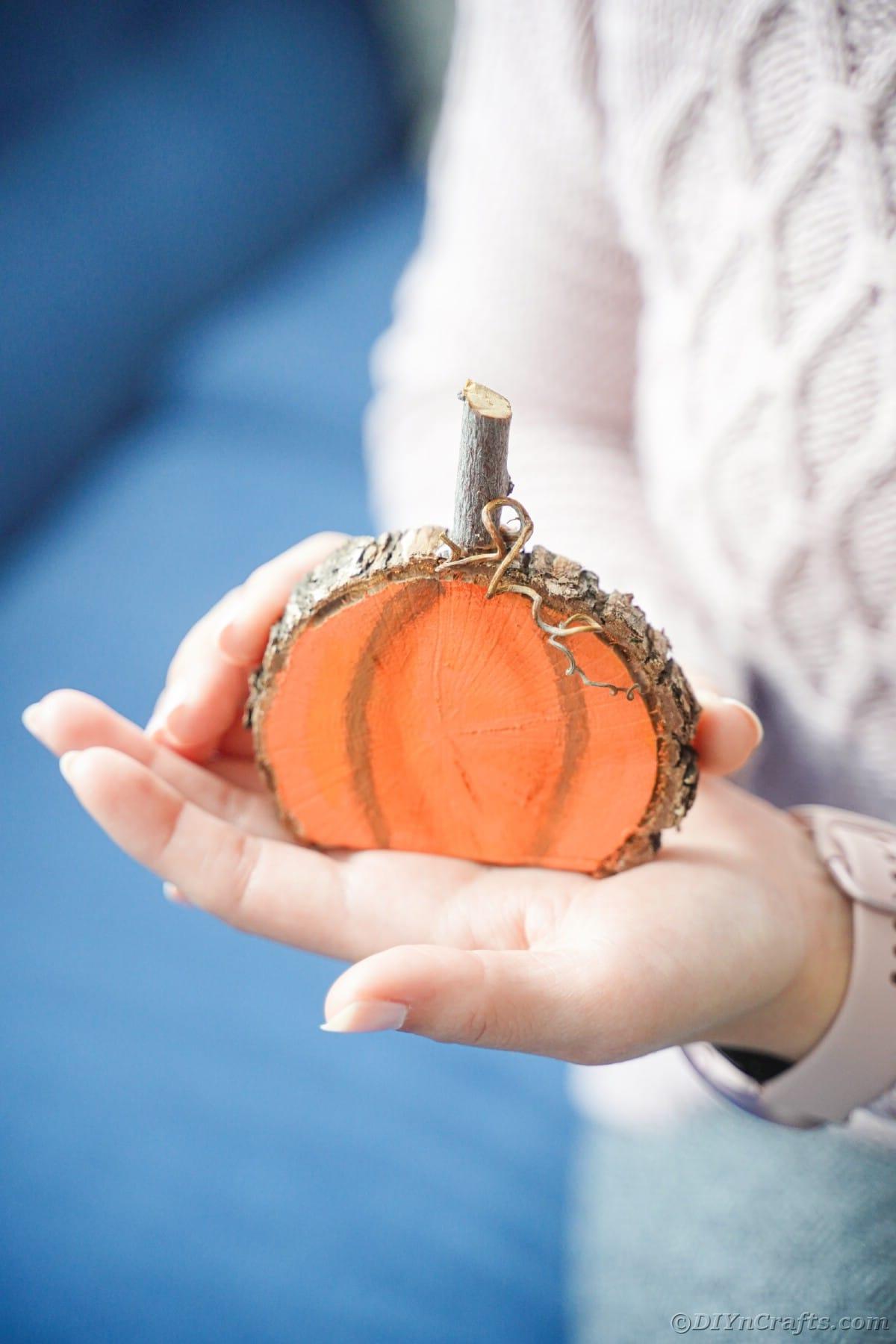 Hand holding wood pumpkin