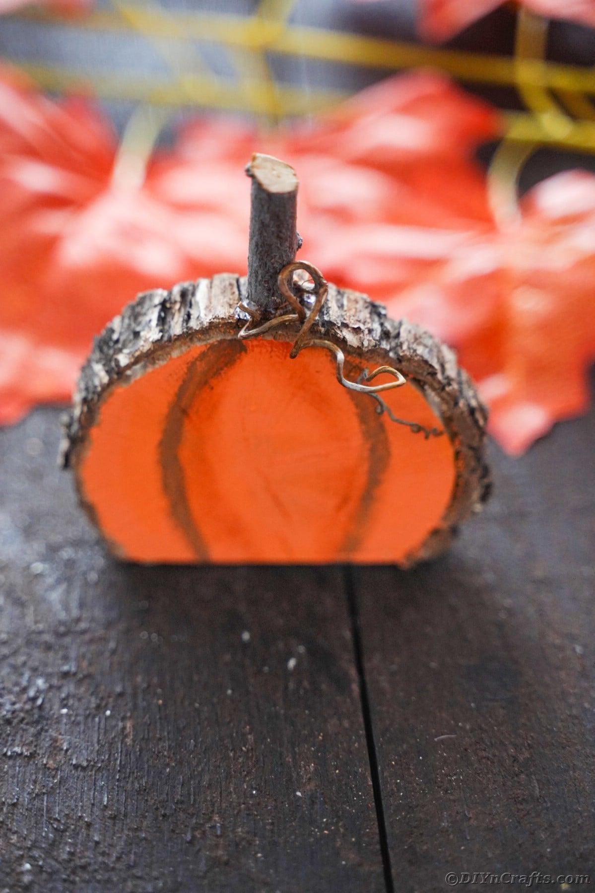 Orange and brown wood slice pumpkin on dark wood table