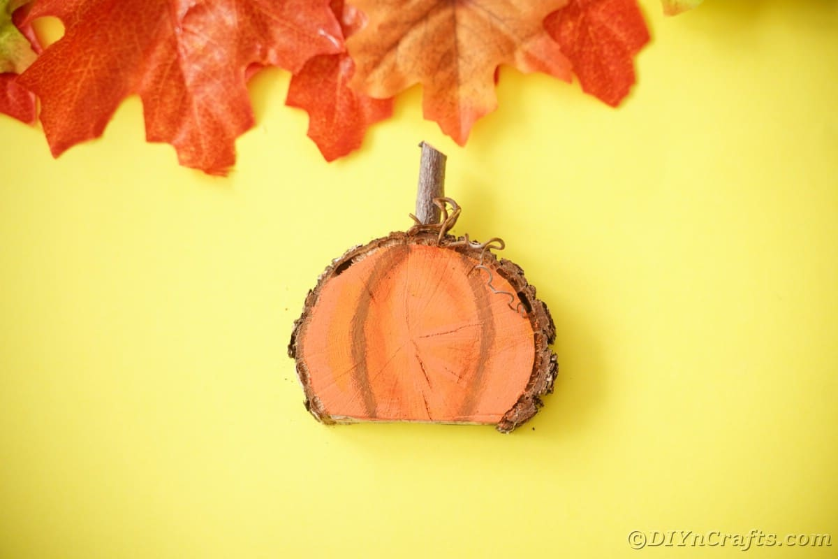 Painted pumpkin from wood slice on yellow surface