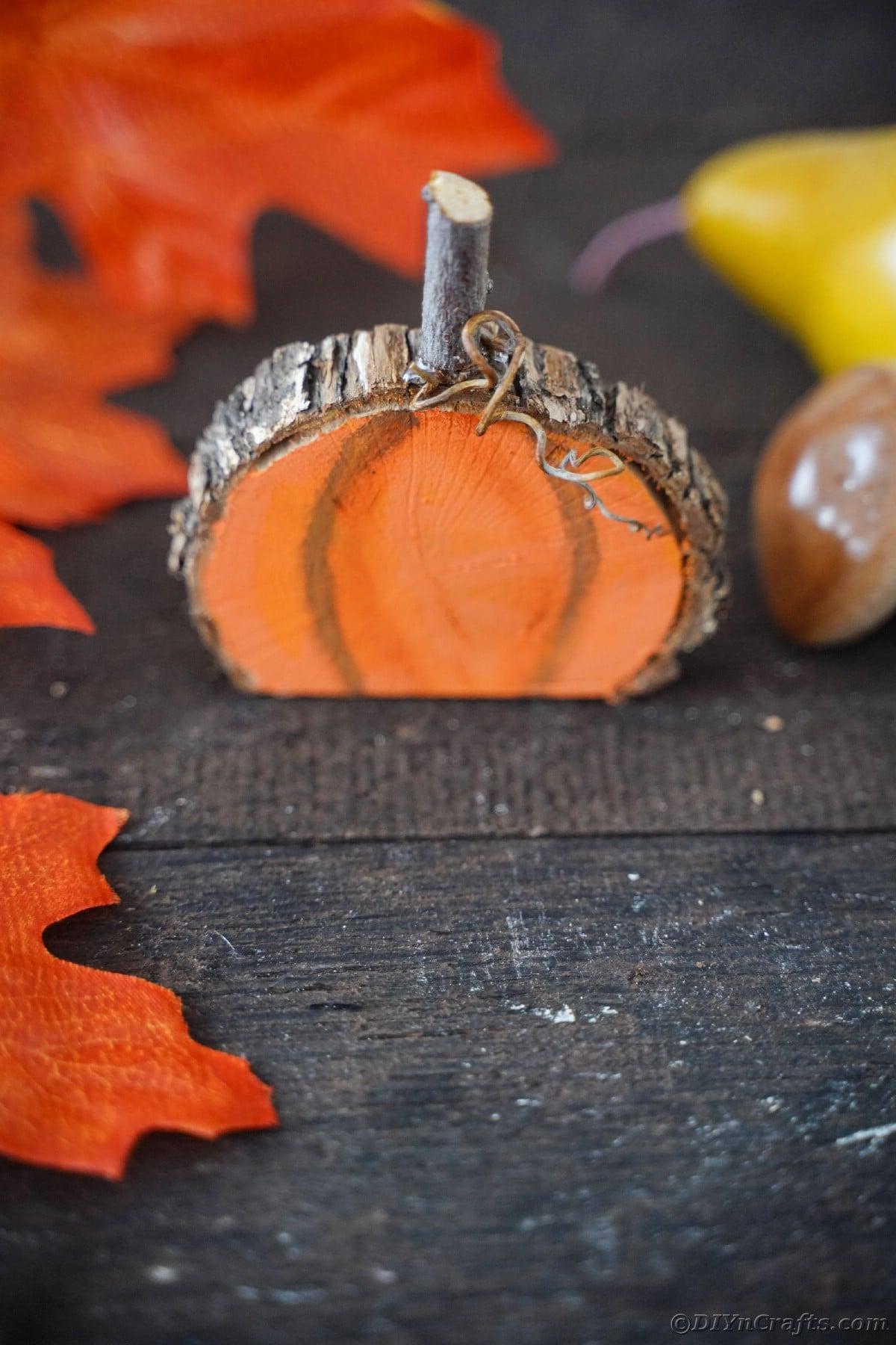 Dark wood table with painted wood slice pumpkin