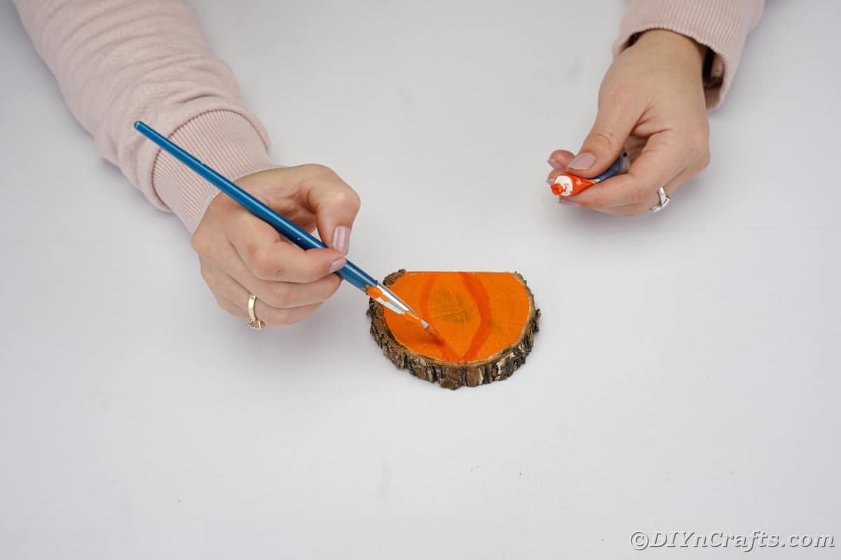 Woman painting red lines on orange painted pumpkin