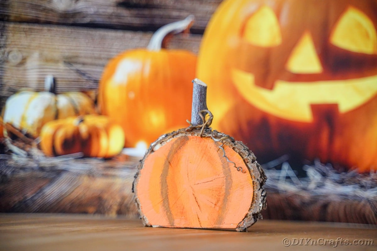 Mini wooden painted pumpkin on table with jack o lantern decor in background