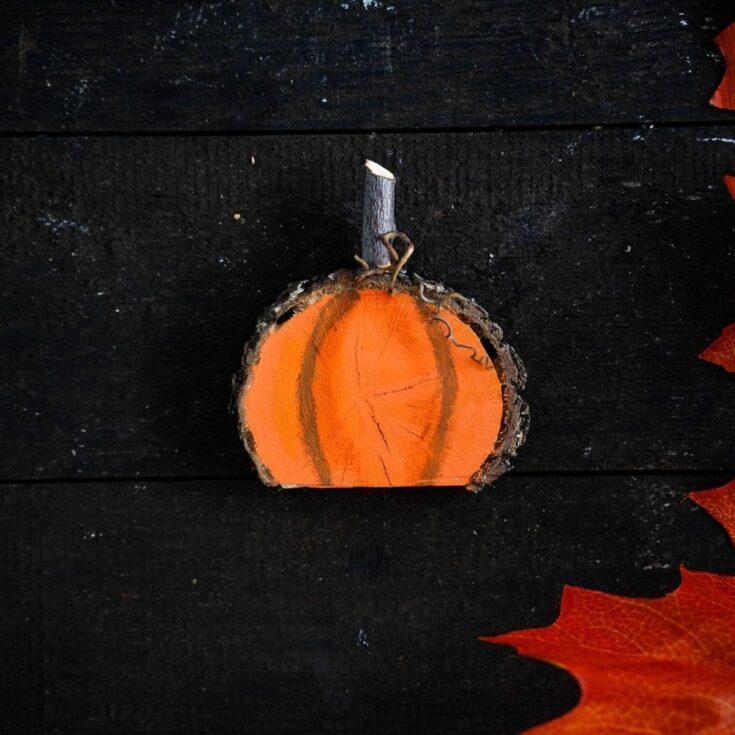 Black table with bright orange painted wood slice pumpkin